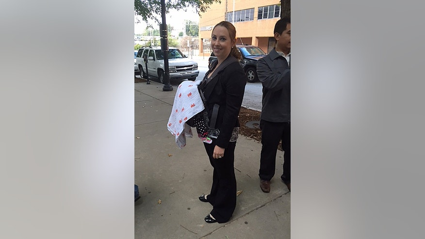 In this Oct 7, 2014 photo released by Stacy Ehrisman-Mickle, Ehrisman-Mickle poses for a photo with her daughter, in Atlanta. Ehrisman-Mickle, an immigration lawyer, brought her 4-week-old baby to court after Immigration Judge J. Dan Pelletier Sr. denied her request to delay a hearing that fell during her maternity leave. During the hearing, her baby began to cry, and Pelletier scolded her for inappropriate behavior. (AP Photo/Stacy Ehrisman-Mickle)
