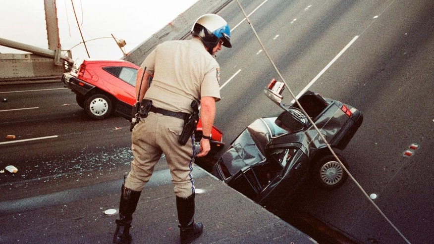 FILE - In this Oct. 17, 1989 file photo, a California Highway Patrol officer checks the damage to cars that fell when the upper deck of the Bay Bridge collapsed onto the lower deck after the Loma Prieta earthquake in San Francisco. Friday is the 25th anniversary of the Loma Prieta earthquake that killed 63 people, injured almost 3,800 and caused up to $10 billion damage. (AP Photo/George Nikitin, File)
