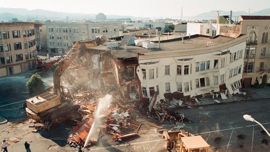 FILE : In this file photo taken Oct. 18, 1989, crews demolish a collapsed apartment building in the Marina district following the Loma Prieta earthquake in San Francisco. Friday is the 25th anniversary of the Loma Prieta earthquake that killed 63 people, injured almost 3,800 and caused up to $10 billion damage. (AP Photo/George Nikitin)