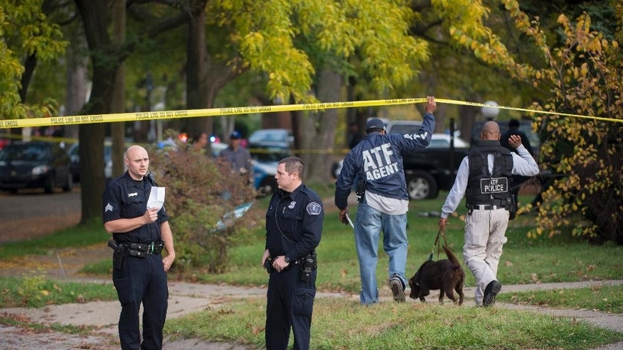 In this photo taken on Thursday, Oct. 16, 2014, Detroit police and investigators work at a crime scene outside a home in Detroit, where a young child was killed and three others were injured. Detroit Police Chief James Craig says a young man and woman have been arrested, but investigators believe there are four more suspects. (AP Photo/Detroit News, David Guralnick)  DETROIT FREE PRESS OUT, HUFFINGTON POST OUT, MAGS OUT, MANDATORY CREDIT