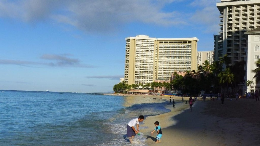 Tourists play in the waves, Friday, Oct. 17, 2014 at Waikiki Beach in Honolulu. Hurricane Ana remained far enough away from the Hawaiian islands to allow tourists to enjoy the mostly sunny weather. (AP Photo/Cathy Bussewitz)