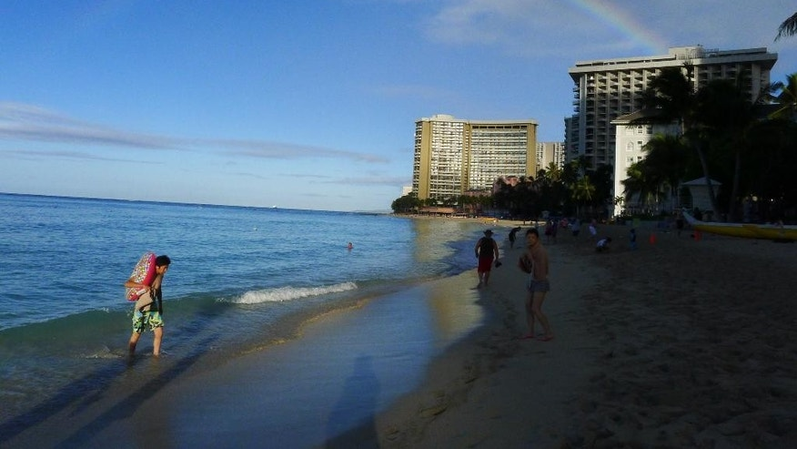Tourists walk by a rainbow, Friday, Oct. 17, 2014 at Waikiki Beach in Honolulu. Hurricane Ana remained far enough away from the Hawaiian islands to allow tourists to enjoy the mostly sunny weather. (AP Photo/Cathy Bussewitz)