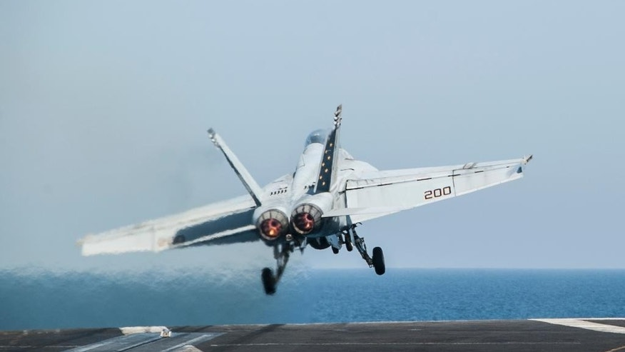 In this photo taken Friday, Oct. 10, 2014, a U.S. Navy aircraft launches from the aircraft carrier USS George H.W. Bush in the Persian Gulf. On Thursday, Oct. 16, the U.S. conducted 14 airstrikes, hitting buildings controlled by the Islamic State group, sniping positions and a heavy machine gun, according to a statement issued by the U.S. military's central command. Over the last two weeks, U.S airstrikes in support of Kurdish fighters in the embattled border town of Kobani, Syria, have killed hundreds of Islamic State fighters, said Rear Adm. John Kirby. (AP Photo/Brian Stephen, U.S. Navy)