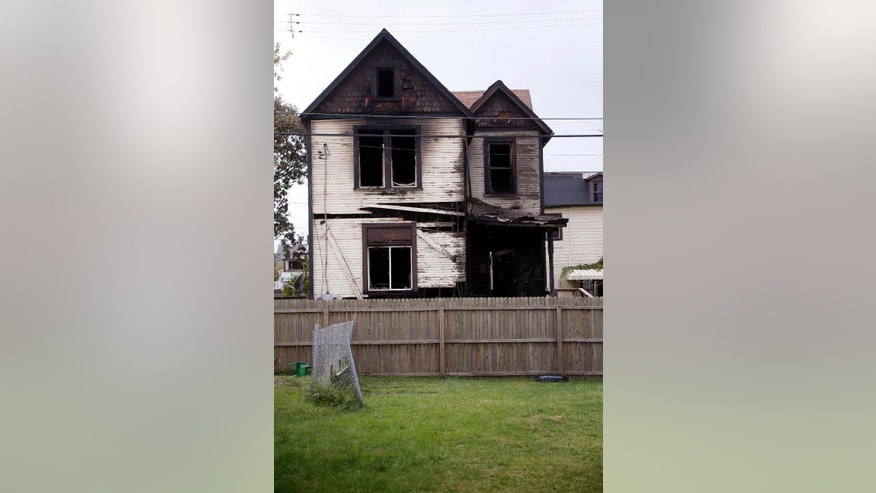 The front of the house in McKeesport, Pa. where a fire killed six members of a family, four of them children, and left another in the hospital in critical condition is visible behind the fence of a neighbors yard on Saturday, Oct. 18, 2014. (AP Photo/Keith Srakocic)