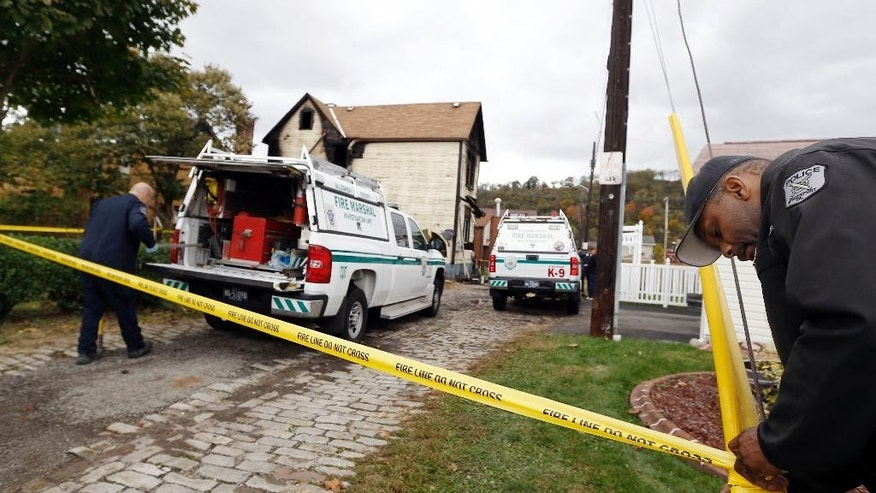 A McKeesport police officer, right, ties fire tape around the scene of the house in McKeesport, Pa., where a fire killed six members of a family, four of them children, and left another in the hospital in critical condition, on Saturday, Oct. 18, 2014. (AP Photo/Keith Srakocic)