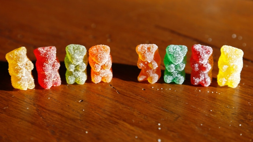 Oct. 17, 2014: Marijuana-infused sour gummy bear candies, left, are shown next to regular ones at right in a photo illustration in Golden, Colorado.