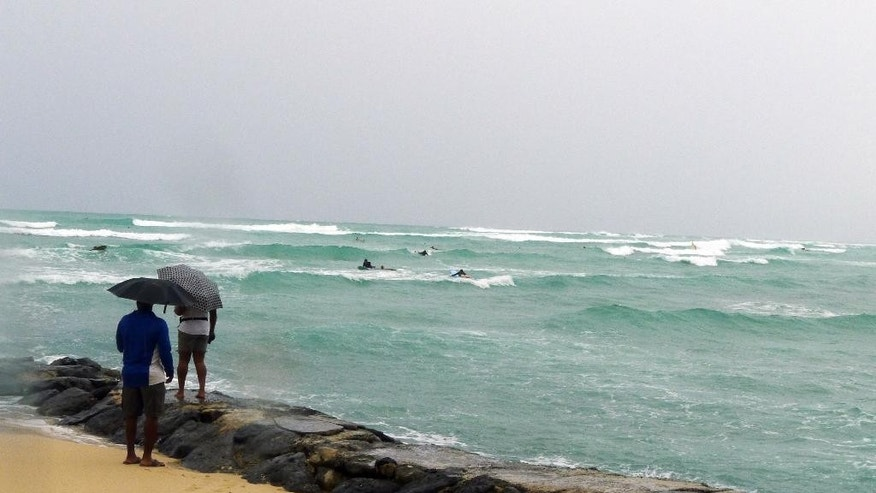 Tourists watch surfers out in choppy waves at Waikiki Beach in Honolulu, Hawaii on Saturday, Oct. 18, 2014, as Hurricane Ana passes southwest of Hawaii. (AP Photo/Cathy Bussewitz)
