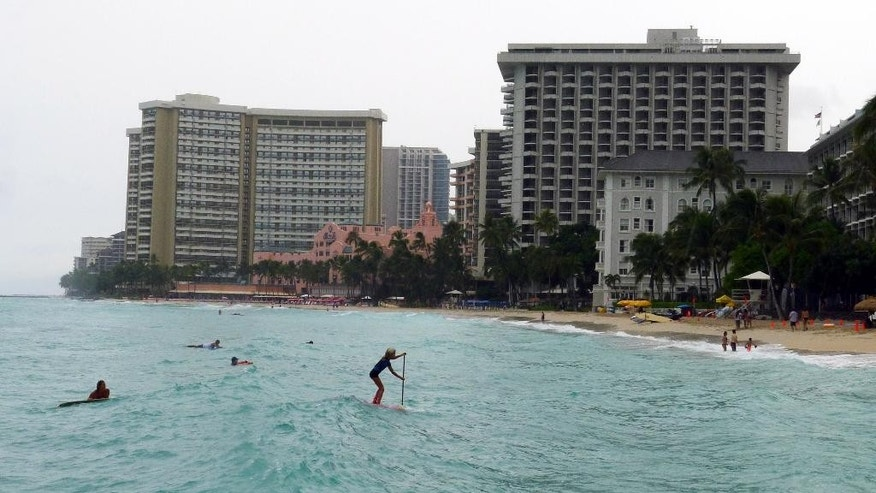 A paddle boarder heads to shore at Waikiki Beach in Honolulu, Hawaii on Saturday, Oct. 18, 2014, as Hurricane Ana passes southwest of Hawaii. (AP Photo/Cathy Bussewitz)