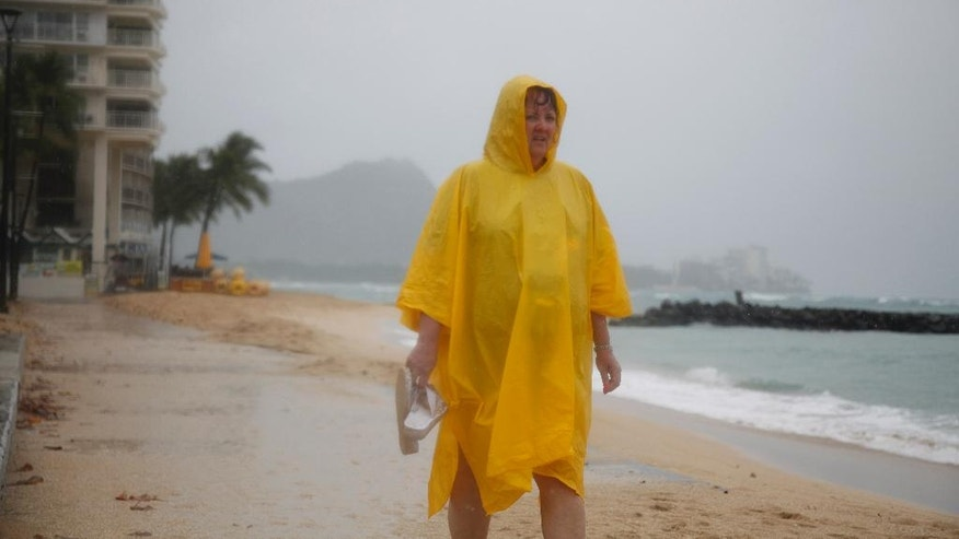 Maryanne Fisher, of League City, Texas, stands in the rain on Waikiki Beach with Diamond Head in the background in Honolulu Sunday, Oct. 19, 2014. Hurricane Ana brought a steady rain to the Hawaiian Island of Oahu as it passed about 180 miles west. Fisher said she plans to spend the rest of the day in the hotel bar with her husband, Mike. (AP Photo/P. Solomon Banda)