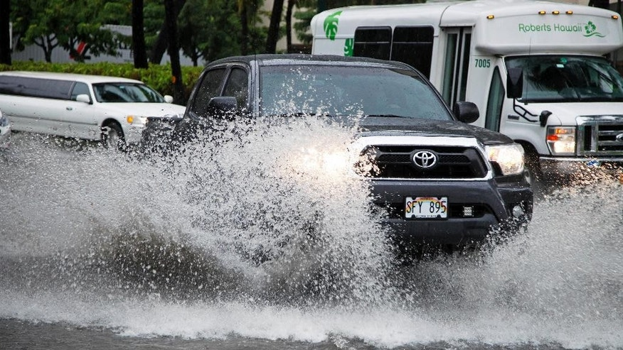 Traffic navigates a flooded street in Waikiki in Honolulu Sunday, Oct. 19, 2014. Hurricane Ana brought a steady rain to the Hawaiian Island of Oahu as it passed about 180 miles west. (AP Photo/P. Solomon Banda)