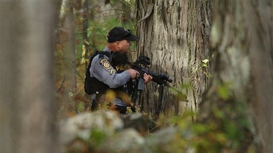 Oct. 18: A Pennsylvania State Trooper searches the woods near Lower Swiftwater Road in Swiftwater, Pa., during a massive manhunt for alleged killer Eric Frein.