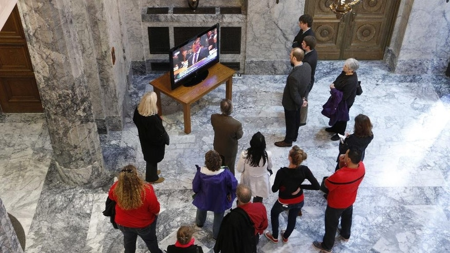 People gather around a television in the lobby of the Washington state Supreme Court to watch oral arguments in a case against Backpage.com, on Tuesday, Oct. 21, 2014, in Olympia, Wash. The court heard a case filed by three sex trafficking victims who say the website helps promote the exploitation of children. (AP Photo/Rachel La Corte)