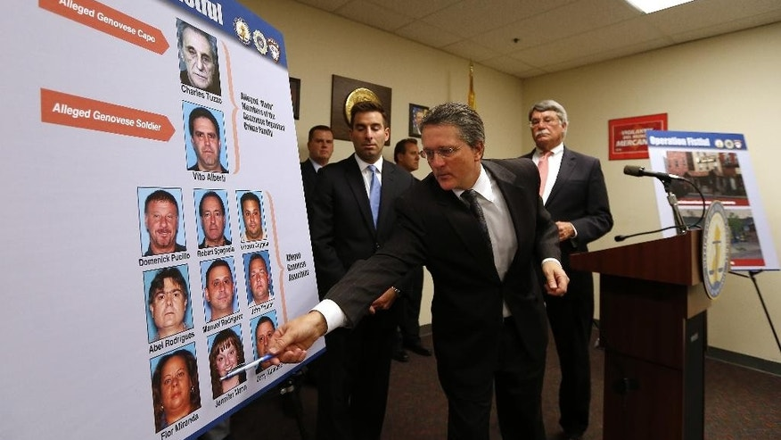 N.J. acting Attorney General John J. Hoffman points to photos of seven alleged members and associates of the New York based Genovese organized crime family who were arrested in Newark, N.J. on Tuesday, Oct 21, 2014.  The attorney general's office alleges the suspects reaped millions of dollars through loansharking, sports gambling, unlicensed check-cashing and money laundering.  (AP Photo/Rich Schultz)
