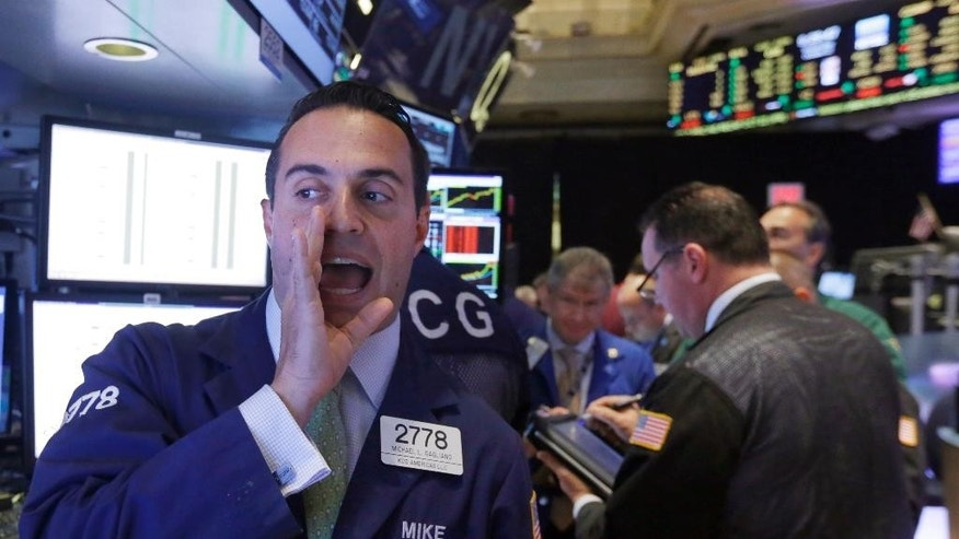 Specialist Michael Gagliano, left, calls out prices as he works at his post on the floor of the New York Stock Exchange, Wednesday, Oct. 22, 2014. Stocks are opening mixed as investors look over earnings reports from U.S. companies. (AP Photo/Richard Drew)