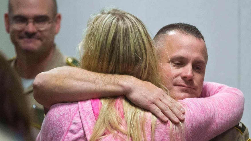 Meridith Berry, Melissa Jenkins' cousin, hugs Capt. Bob Cushing of the Vermont State Police, Wednesday, Oct. 22, 2014, in Vermont Superior Court in Burlington, Vt., after Allen Prue was found guilty of first-degree murder for the 2012 slaying of Jenkins. (AP Photo/The Burlington Free Press, Glenn Russell, Pool)