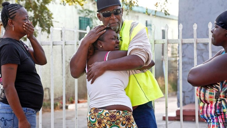 Danisha Mitchell is hugged by a relative at the scene of the accident Thursday, Oct. 23, 2014, a day after her 7-year-old son Jamarion Thomas was killed in when his motorized bicycle collided with an ice cream truck, in South Los Angeles. The driver of the ice cream truck was attacked by neighborhood residents after it struck and killed the boy and was taken to a police station for his protection. The child had been riding the bike alongside the ice cream truck when he apparently slipped, was caught under a rear wheel and run over, Sgt. Timothy Colson said. The collision was an accident, and the driver has not been charged, police said. (AP Photo/Nick Ut)
