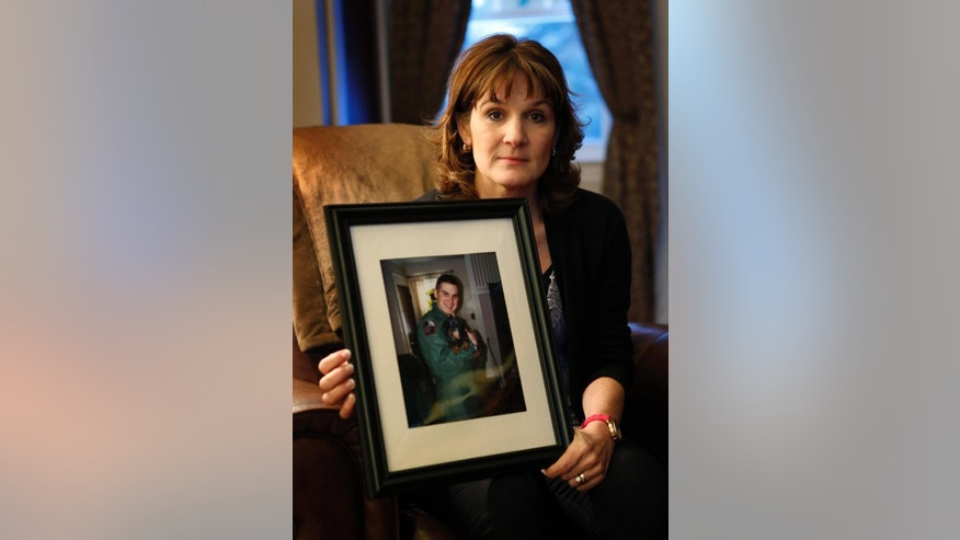 FILE - In this Dec. 17, 2013 file photo, Hallie Twomey poses with a photo of her son, C.J., at her home in of Auburn, Maine. C.J. committed suicide three and a half years earlier. On Thursday, Oct. 23, 2014, a rocket containing a vial of C.J.'s ashes was launched from the New Mexican desert into space before landing in the White Sands Missile Range. His ashes had previously been released in nearly all 50 states and dozens of places overseas.  (AP Photo/Robert F. Bukaty, File)