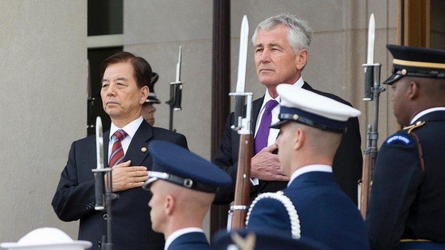 National anthems are played as Defense Secretary Chuck Hagel, right, stands with Korean National Defense Minister Han Min Koo as he arrives for an honor cordon at the Pentagon, Thursday, Oct. 23, 2014. (AP Photo/Carolyn Kaster)