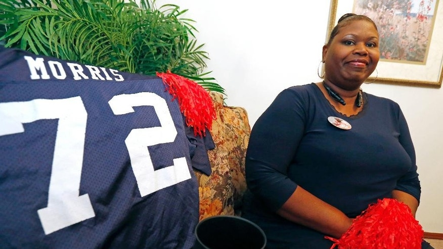 In this photo taken on Thursday, Oct. 16, 2014, lifelong Mississippi resident Logenvia Morris poses at her home in  Jackson, Miss., next to her prize possession, the first Mississippi game jersey her son Aaron Morris wore for the football team. Morris, who goes to every football game to cheer for her son, said the offensive lineman had to overcome his grandfather's deep skepticism about whether black students are truly welcome at the university. The warm welcome extended to both mother and son during a recruiting visit by students and players are among the main reasons the Morris family were quick to join the Ole Miss family. (AP Photo/Rogelio V. Solis)
