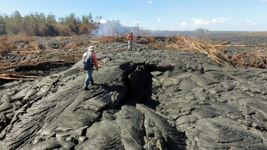 In this Oct. 22, 2014 photo provided by the U.S. Geological Survey, geologists walk over the surface of the flow to track surface breakouts along a portion of the flow margin, about a kilometer upslope of the flow front. A 13-mile finger of lava from Kilauea Volcano has started to again move quickly, and could hit a secondary road sometime Friday, Oct. 24, 2014. Officials on Hawaii's Big Island won't start evacuating people until the lava flow is within three to five days of affecting Pahoa residents. (AP Photo/U.S. Geological Survey)