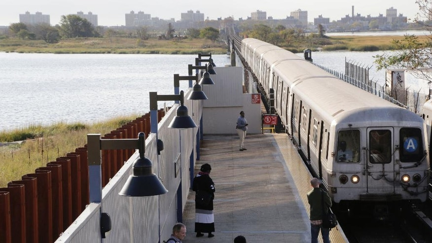 In this Oct. 21, 2014 photo, a subway train slows as it makes its way into the Broad Channel station in the Rockaways section of the Queens borough of New York. On the left is a steel seawall installed after Superstorm Sandy washed out sections of the tracks in October 2012. (AP Photo/Mark Lennihan)