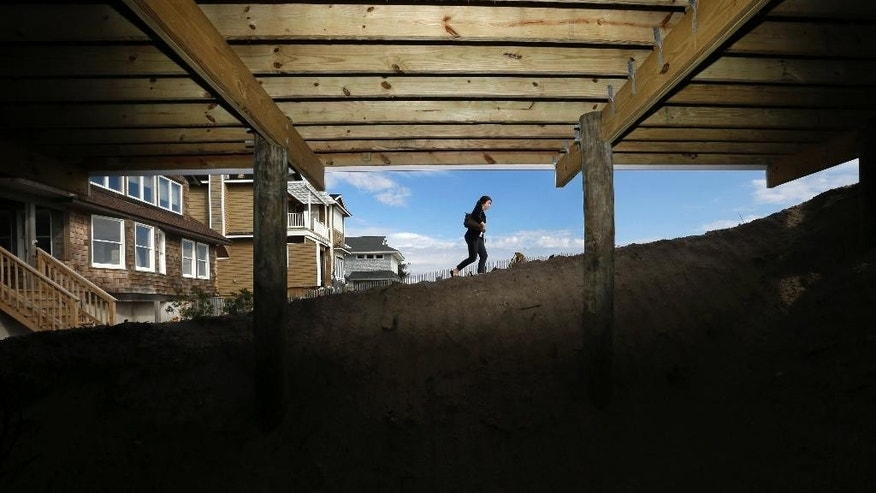 In this Oct. 21, 2014 photo, a woman walks on a dune in Mantoloking, N.J., near a home that is being raised after being damaged by Superstorm Sandy nearly two years ago. After Superstorm Sandy, New York and New Jersey officials vowed to make sure the unprecedented destruction wouldn't happen again. But many planned projects are still far off, and thousands of homeowners await repair aid, some of it coupled with steps to make homes safer. (AP Photo/Mel Evans)