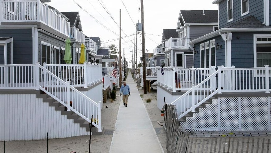 In this Oct. 15, 2014 photo, a man walks on a sidewalk in the Breezy Point neighborhood in the Queens borough of New York. Two years ago a fire raged across this oceanfront community during Superstorm Sandy, destroying 130 homes, including those that lined this walk. The new houses are all built on elevated concrete foundations to protect them from future storms. (AP Photo/Mark Lennihan)