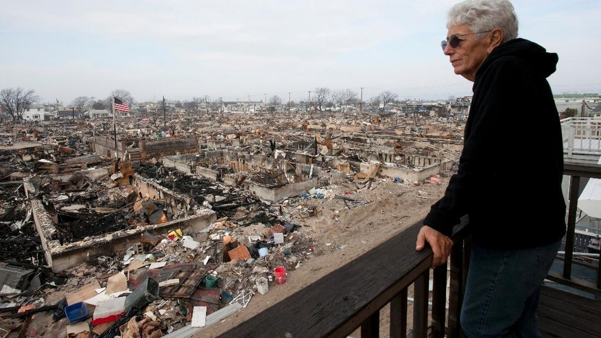 In this Dec. 4, 2012 photo, Anne Hoerning looks from her second floor balcony at the remains of the over 100 houses that burned during Superstorm Sandy in the Breezy Point section of the Queens borough of New York. Hoerning's house was scorched by the flames and flooded by seawater but did survive. (AP Photo/Mark Lennihan)