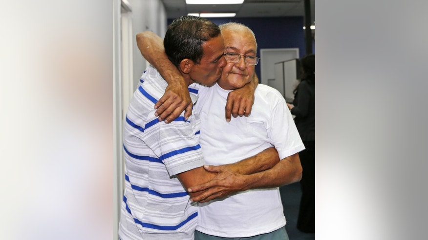 Rafter Joel Moreno, left, rescued near Miami, kisses his father Luis Felipe Moreno, right, who left Cuba in the 1980 Mariel boat lift and have been separated since then,  Tuesday, Oct. 28, 2014, in Miami.  Moreno, 39, says the men traveled in a homemade raft powered by a boat motor and could see lights off the coast of Florida within six hours of leaving Cojimar, Cuba. The motor ran out of gas before they reached shore. On their second day at sea, a strong wave overturned the raft, dumping all their water and food into the ocean. On Sunday, Moreno decided to break the raft apart, giving each man a piece to hold and try to swim to shore. Authorities have located 11 of the men. Two remain missing. (AP Photo/Alan Diaz)