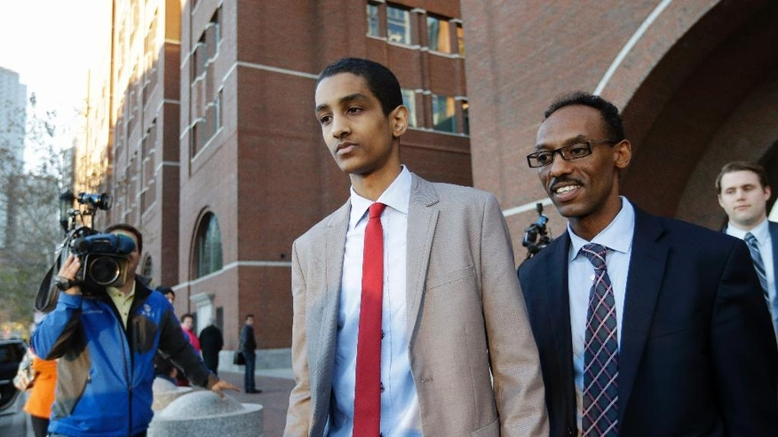 Robel Phillipos, center, a college friend of Boston Marathon bombing suspect Dzhokhar Tsarnaev, departs federal court with defense attorney Derege Demissie, right, following jury deliberations in his trial, Monday, Oct. 27, 2014, in Boston. Phillipos is accused of lying about being in Tsarnaev's dorm room three days after the deadly bombing, when two other friends removed a backpack containing fireworks and other potential evidence. (AP Photo/Steven Senne)