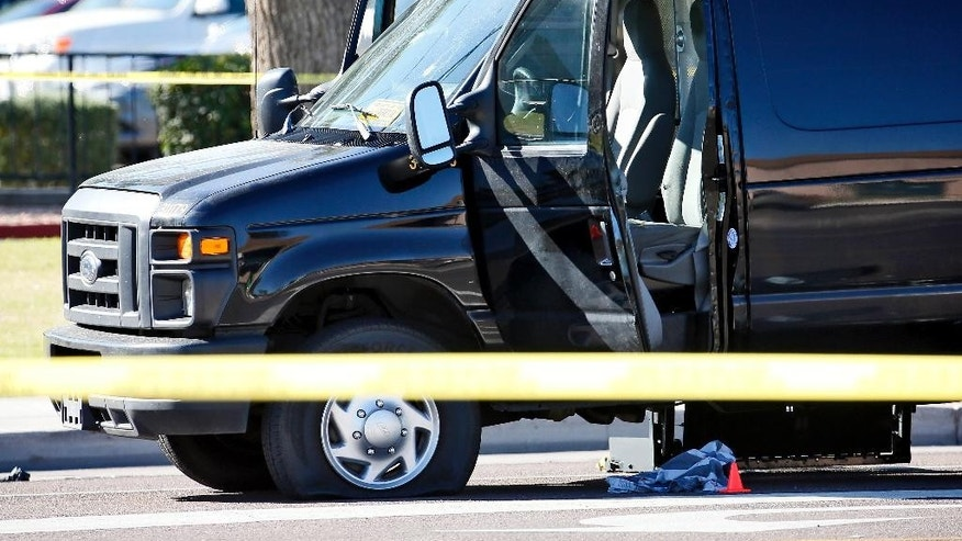 A van with multiple bullet holes and a prisoner uniform lying on the ground is shown at the scene of an officer involved shooting, Tuesday, Oct, 28, 2014 in Phoenix. A sheriff's detention officer shot and wounded a jail inmate who was struggling with another officer after he slipped out of restraints and ran away while being taken to a hospital in Phoenix, authorities said Tuesday. The inmate remains hospitalized. (AP Photo/Matt York)
