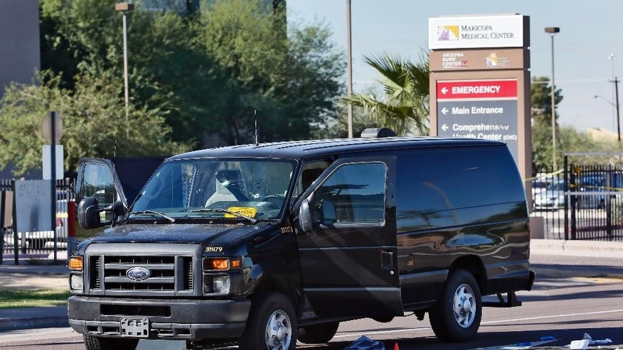A van with multiple bullet holes is shown at the scene of an officer involved shooting, Tuesday, Oct, 28, 2014 in Phoenix. A sheriff's detention officer shot and wounded a jail inmate who was struggling with another officer after he slipped out of restraints and ran away while being taken to a hospital in Phoenix, authorities said Tuesday. The inmate remains hospitalized. (AP Photo/Matt York)