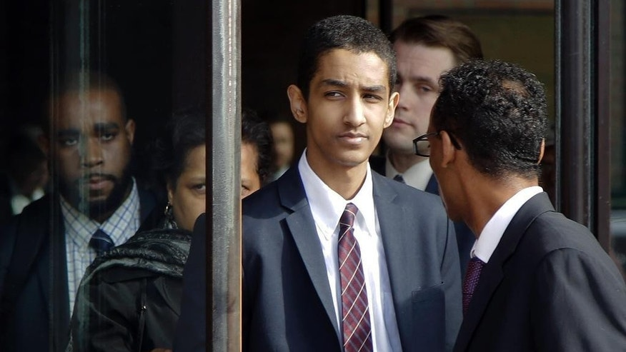Robel Phillipos, center, departs federal court with defense attorney Derege Demissie, right, after he was convicted in Boston Tuesday, Oct. 28, 2014 on two counts of lying about being in the dorm room of Boston Marathon bombing suspect Dzhokhar Tsarnaev three days after the bombing in 2013, while two other friends removed a backpack containing fireworks and other potential evidence. (AP Photo/Stephan Savoia)