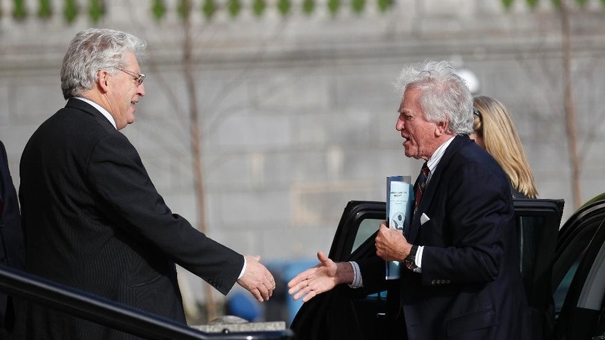 The newly appointed U.S. envoy to Northern Ireland, former Sen. Gary Hart, right, is greeted by Alasdair McDonnell, leader of the Social Democratic and Labour Party as he arrives at Parliament Buildings, Stormont, in Belfast, Northern Ireland, Wednesday, Oct. 29, 2014. Hart is scheduled to meet the leaders of all five parties in Northern Ireland's unity government Wednesday and Thursday. Hart is seeking to broker compromise on a wide range of issues threatening to tear apart the 7-year-old coalition of British Protestants and Irish Catholics. (AP Photo/Peter Morrison)