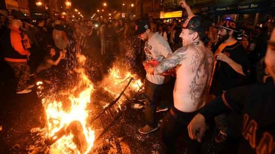 October 29, 2014: San Francisco Giants fans celebrate next to debris that has been set on fire in the Mission district after the San Francisco Giants beat the Kansas City Royals to win the World Series.  (AP Photo/Noah Berger)