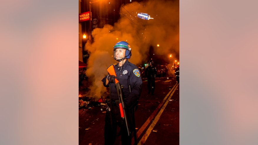 A beer can hurled by a reveler passes over a police officer  in the Mission district after the San Francisco Giants beat the Kansas City Royals to win the World Series on Wednesday, Oct. 29, 2014, in San Francisco. (AP Photo/Noah Berger)