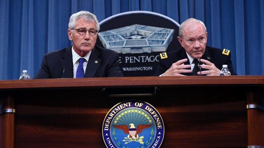 Defense Secretary Chuck Hagel listens at left at Joint Chiefs Chairman Gen. Martin E. Dempsey speaks during a briefing at the Pentagon, Thursday, Oct. 30, 2014. (AP Photo/Susan Walsh)
