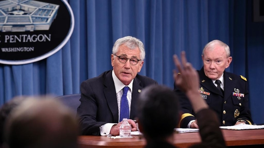Defense Secretary Chuck Hagel, accompanied by Joint Chiefs Chairman Gen. Martin E. Dempsey, takes a question during a briefing at the Pentagon, Thursday, Oct. 30, 2014. Hagel ordered military men and women helping fight Ebola to undergo 21-day quarantines that start upon their return _ instead of their last exposure to an Ebola patient. (AP Photo/Susan Walsh)