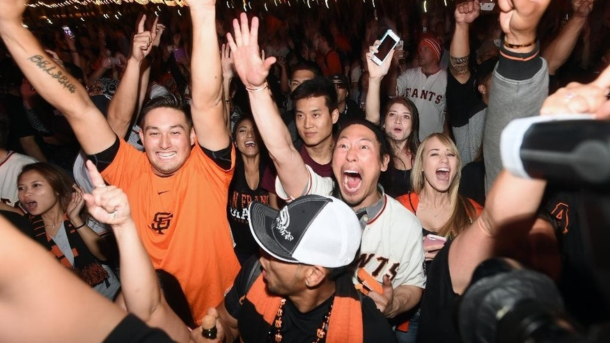 San Francisco Giants fans celebrate after the Giants won Game 7 to win the World Series baseball game between the San Francisco Giants and Kansas City Royals at Civic Center Plaza on Wednesday, Oct. 29, 2014, in San Francisco.  (AP Photo/Noah Berger)