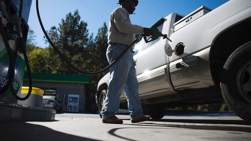 Motorist Jerry Reed fills up his tank at a gas station, Thursday, Oct. 30, 2014, in Atlanta. Almost unbelievably, the national average price of a gallon of gasoline is back under $3 for the first time since December 2010. (AP Photo/David Goldman)