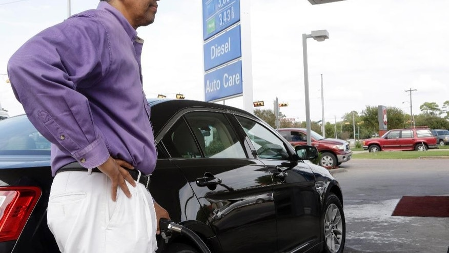 In this Oct. 29, 2014 photo, Mikel Marshall fills his car with gasoline at a Mobil station in Houston, where regular gas was available for $2.85 per gallon. The U.S. is on track for the lowest annual average gas price since 2010 _ and the 2015 average is expected to be lower even still. (AP Photo/Pat Sullivan)