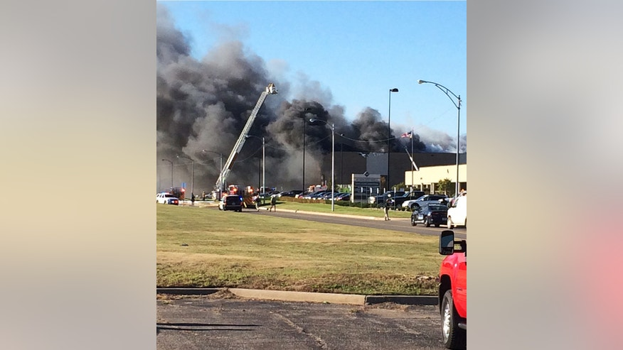In this photo provided by Jay Boyle, emergency vehicles and first responders are on the scene of a small plane crash at Wichita Mid-Continent Airport in Wichita, Kan., Thursday, Oct. 30, 2014. A small plane lost power after takeoff and crashed into a building while trying to return to a Kansas airport Thursday, killing at least four people. (AP Photo/Jay Boyle)