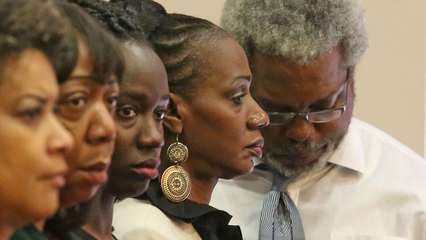 Family members, Pam Champion, mother, second right, and Robert Champion Sr., father, right, parents of Robert Champion Jr. as the verdict is read Friday, Oct. 31, 2014 after a jury found Dante Martin, a former member of Florida A&M University's Marching 100 band guilty of manslaughter in the fatal hazing of Champion. Martin, who faces up to 22 years in prison, showed no emotion as Circuit Judge Renee Roche read the verdict. He was also found guilty of felony hazing and two misdemeanor counts of hazing involving two other band members. (AP Photo/Orlando Sentinel, Red Huber, Pool)