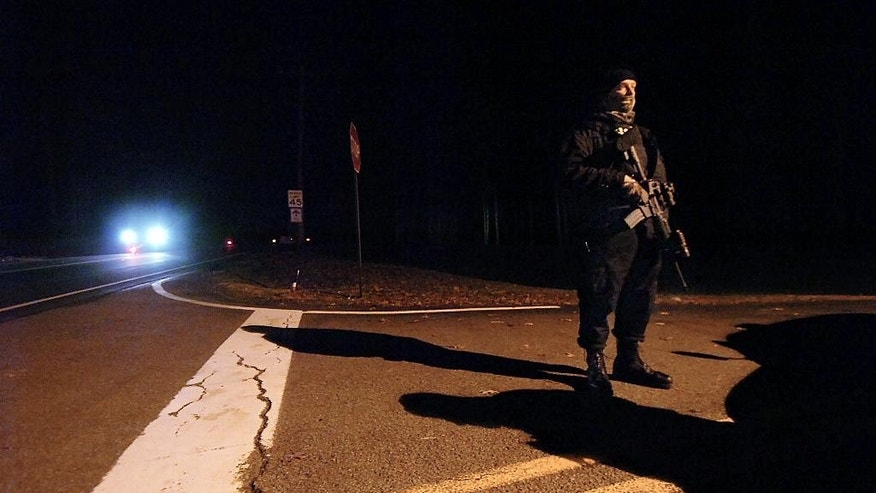 A Pennsylvania State Police Trooper stands guard in front of the Blooming Grove State Police barracks after suspected killer Eric Frein was captured and taken into custody at the barracks early Friday, Oct. 31, 2014, in Blooming Grove Township, Pennsylvania.    (AP Photo / The Scranton Times-Tribune, Butch Comegys)
