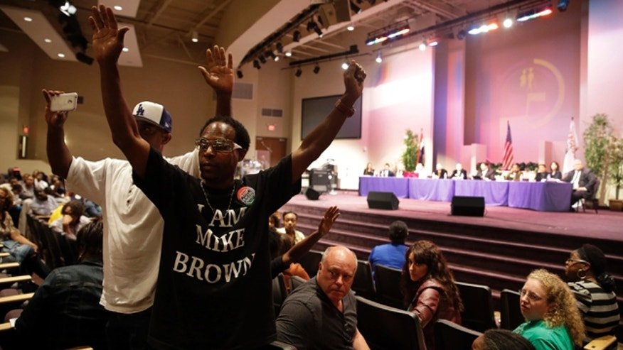 September 9, 2014: Maurice Brown raises his arms during a public comments portion of a meeting of the Ferguson City Council.