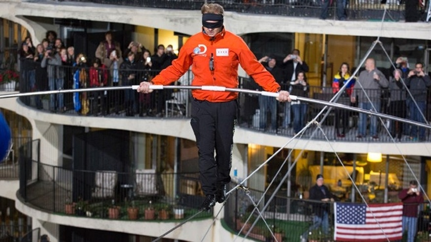 Nov. 2, 2014: This photo provided by Discovery Communication shows Nik Wallenda walking across the Chicago skyline blindfolded for Discovery Channel's Skyscraper Live with Nik Wallenda.