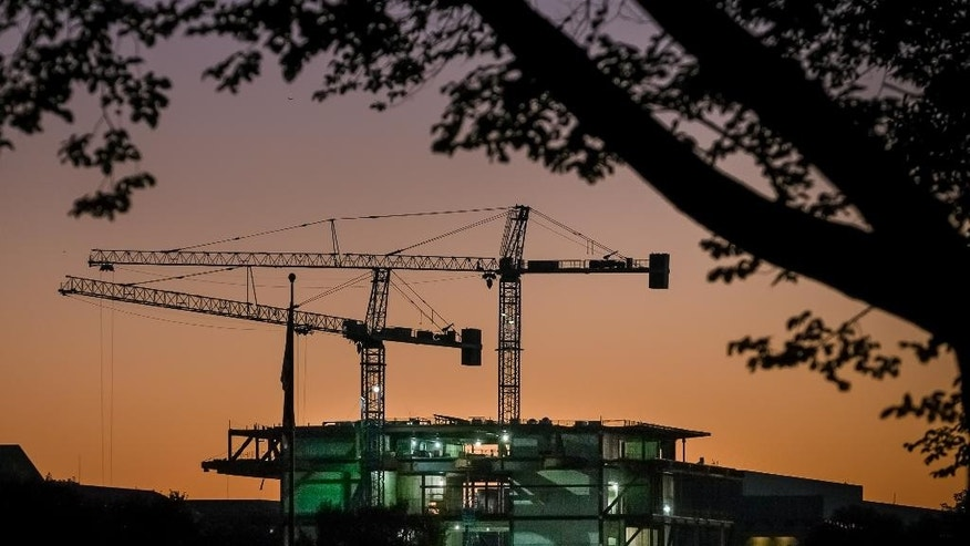 In this Oct. 8, 2014 photo, construction cranes are silhouetted against the early morning sky as work continues on Smithsonian's new National Museum of African American History and Culture in Washington. The Commerce Department releases construction spending for September on Monday, Nov. 3, 2014. (AP Photo/J. David Ake)