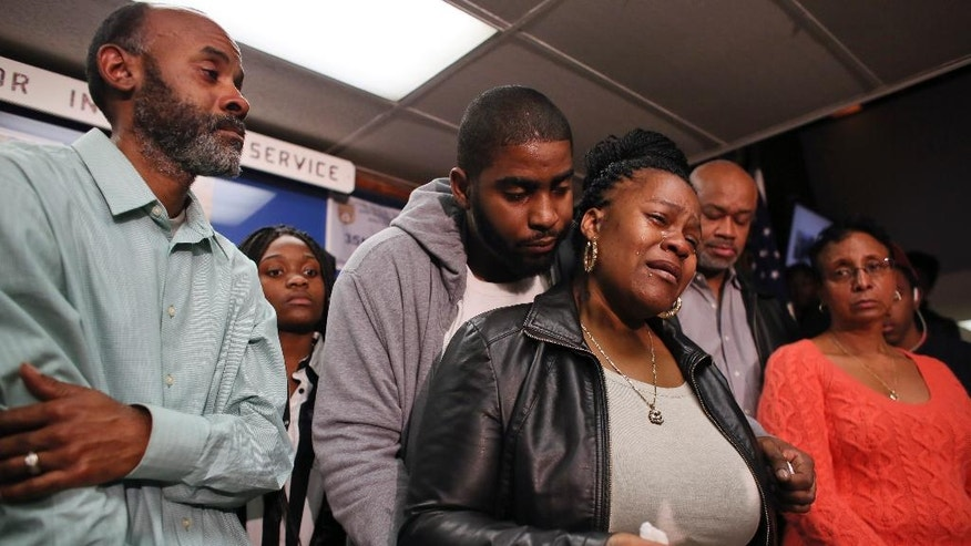 Family members surround Keisha Gaither, third from left, mother of kidnapping victim Carlesha Freeland-Gaither, during a news conference in Philadelphia on Tuesday, Nov. 4, 2014.  The reward is up to $15,000 for information leading to an arrest in the reported abduction of Carlesha Freeland-Gaither. The Fraternal Order of Police added its own $5,000 reward Tuesday to the $10,000 the city approved Monday for information on the disappearance of 22-year-old Freeland-Gaither. Detectives say a witness reported seeing a woman identified as Freeland-Gaither yelling for help as she was forced into a dark gray four-door vehicle at about 9:40 p.m. Sunday in Germantown. (AP Photo/ Joseph Kaczmarek)