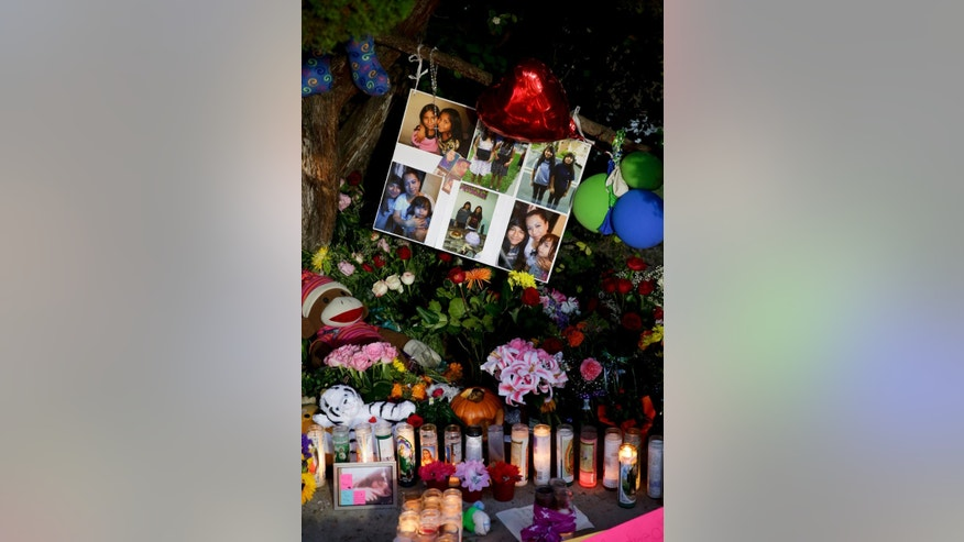 Photographs of twin sisters Lexia  and Lexandra Perez are displayed at a makeshift memorial near where they and Andrea Gonzales were killed in a hit and run on Halloween, Monday, Nov. 3, 2014, in Santa Ana, Calif. (AP Photo/Chris Carlson)