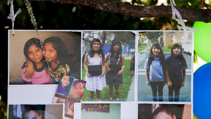 Photographs of twin sisters Lexia, left, and Lexandra Perez are displayed at a makeshift memorial near where they and Andrea Gonzales were killed in a hit and run on Halloween, Monday, Nov. 3, 2014, in Santa Ana, Calif. (AP Photo/Chris Carlson)